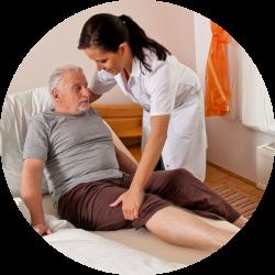 Un homme âgé est manutentionné par une aide soignante
